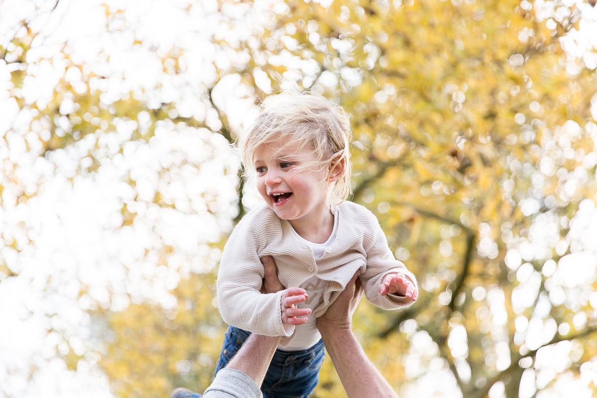 Meisje vliegend door de lucht met herfstbladeren op de achtergrond gemaakt door Dasja Dijkstra fotograaf van Das Knuss Fotografie Coronaproof op de foto